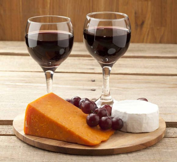 Close-up shot of cheese, grapes and wine glass on wooden board.